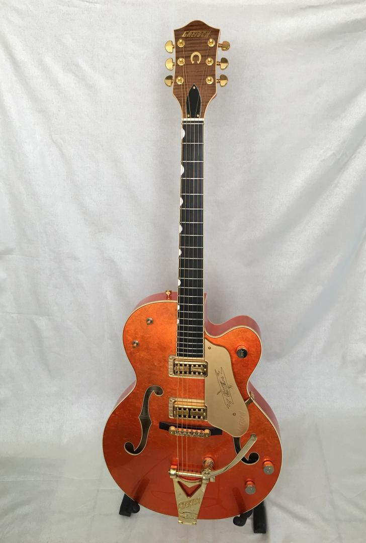 GRETSCH GUITARE ELECTRIQUE CHET ATKINS PROFESSIONNEL COLLECTION USA LIMITEE A 25 EXEMPLAIRES DANS LE MONDE. FABRIQUEE PAR LE MAITRE LUTHIER GRETSCH STEPHEN STERN. FINITIONS FEUILLES D'OR FIN. CORPS & MANCHE ERABLE TOUCHE EBENE. 2 MICROS TV JONES. VOL. TON. SELECTEUR. MECANIQUES ROTOMATIC GROVER. VIBRATO BIGSBY. ACCASTILLAGE PLAQUE OR. CORDE OR 24 CARAT. LIVREE AVEC ETUI FACON CROCODILE. SANGLE ET MEDAILLON CEINTURON CUIR NATUREL FACONNE A LA MAIN PAR TOM NIX.
